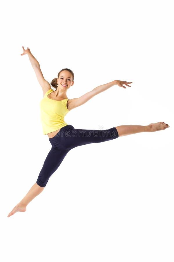 Schöne sportliche Frau, die auf einen weißen Hintergrund springt stockbild