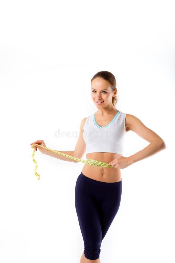 Schöne sportliche Frau, die ein Meter hält und auf einem weißen Ba lächelt lizenzfreie stockbilder
