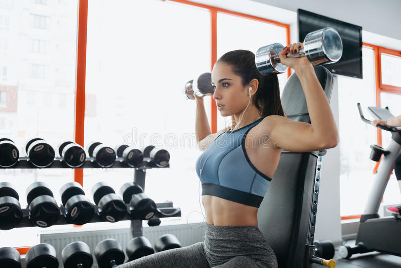 Schöne sportliche Frau, die Machteignungsübung an der Sportturnhalle tut stockbild