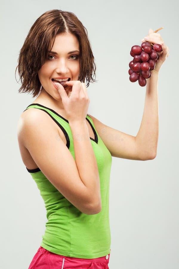 Schöne sportliche Frau, die Trauben isst stockfotografie