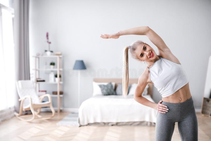 Schöne sportliche Frau, die zu Hause Übung tut stockbild