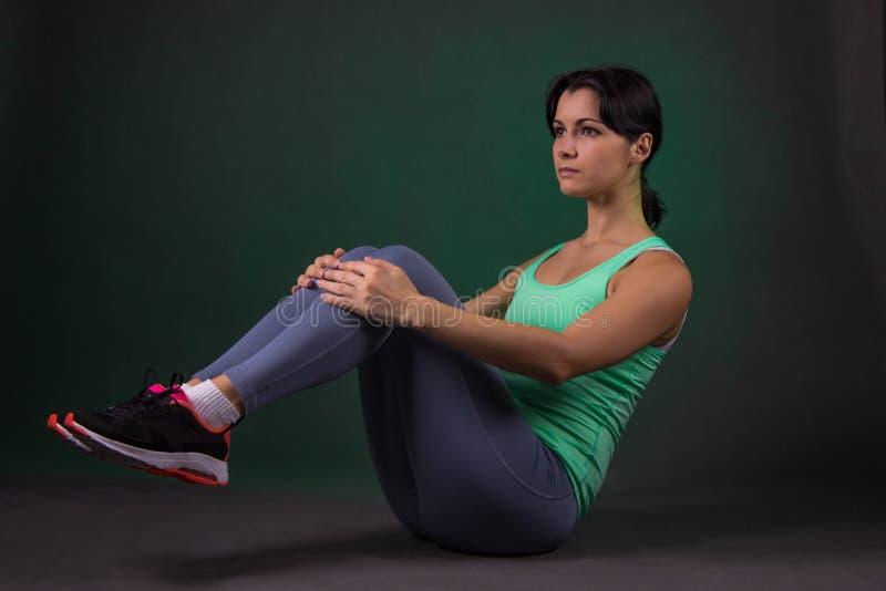 Schöne sportliche Frau, Eignungsfrau, die Übung auf einem dunklen Hintergrund mit grüner Hintergrundbeleuchtung tut stockbild