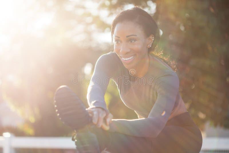 Schöne sportliche Frau mit einem reizend Lächeln, das ihre Beine ausdehnt lizenzfreies stockbild