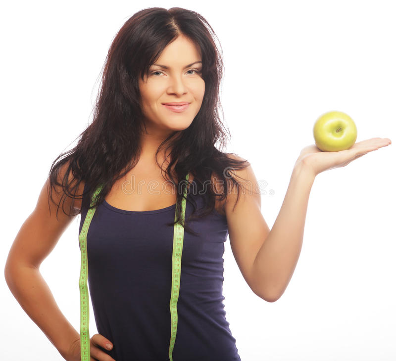 Schöne sportliche Frau mit grünem Apfel und messendem Band lizenzfreies stockfoto