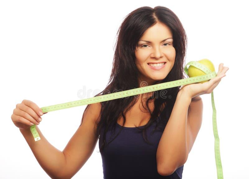 Schöne sportliche Frau mit grünem Apfel und messendem Band stockfoto
