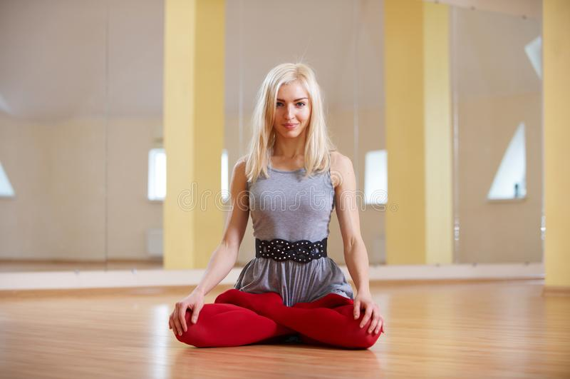 Schöne sportliche Sitzjogifrau übt Yoga asana Padmasana - Lotus-Haltung im Eignungsraum lizenzfreies stockbild