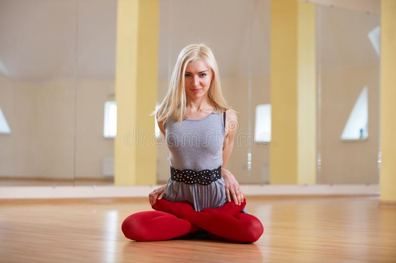 Schöne sportliche Sitzjogifrau übt Yoga asana Padmasana - Lotus-Haltung im Eignungsraum lizenzfreies stockfoto