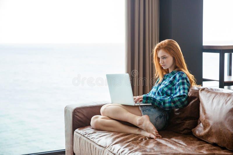 Schöne starke Dame, die auf Couch sitzt und Laptop verwendet lizenzfreies stockfoto