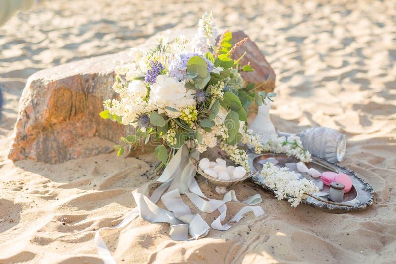 Schöne stilvolle Dekoration mit einem Blumenstrauß und Makronen nahe dem Stein auf dem Strand von einem Meer Wedding Auslegung stockbilder