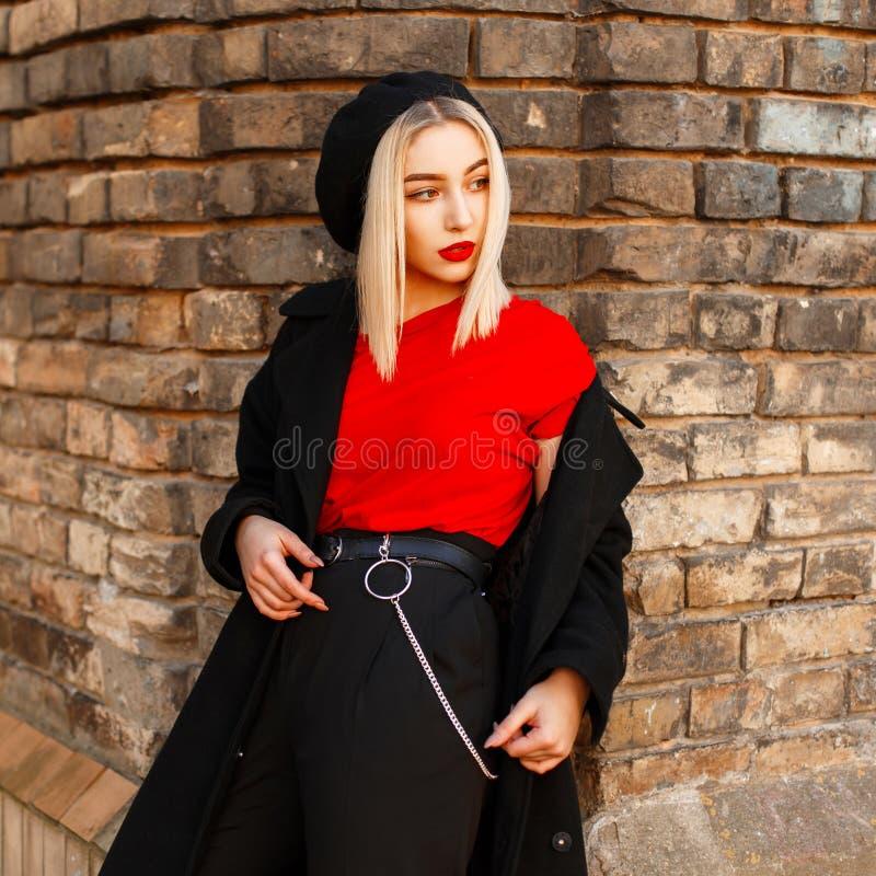 Schöne stilvolle Frau in einem modischen schwarzen Mantel nahe einer Backsteinmauer stockfotos