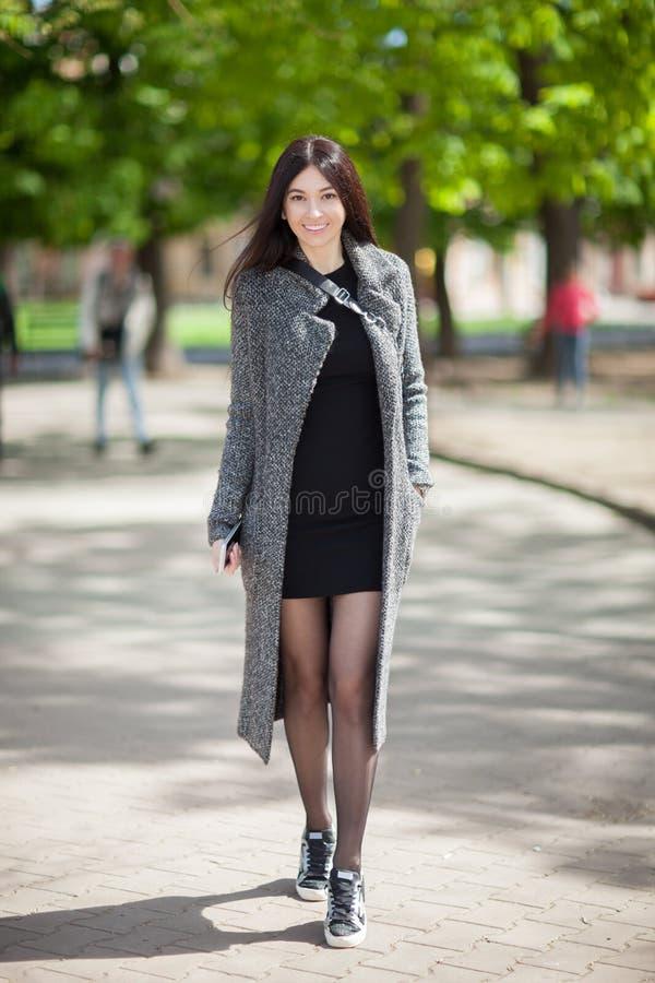 Schöne stilvolle Frau im schwarzen Kleid und im gemütlichen Regenmantelweg im Stadtpark Lebensstil des Frühlinges im Freien Gl?ck stockfoto