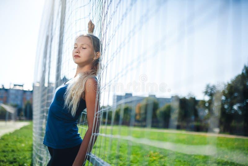 Schöne stilvolle Frau mit geschlossenen Augen in einem blauen Hemd und in den Gamaschen steht nahe einem Fußballziel am Stadion b stockbild