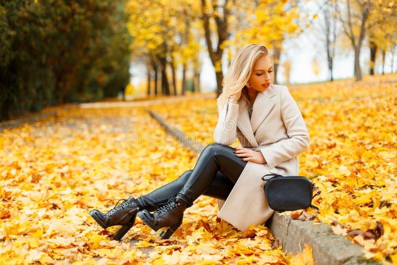 Schöne stilvolle junge blonde Frau in einem modischen Mantel stockbilder