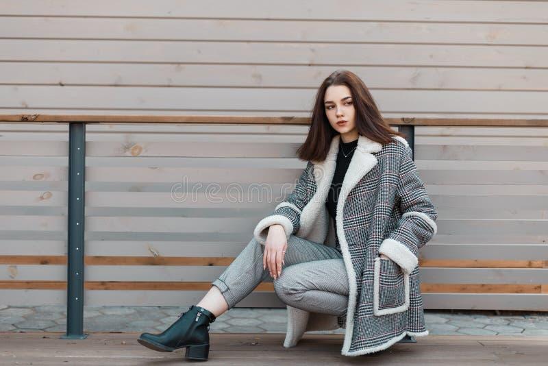 Schöne stilvolle junge Frau in den modernen grauen Hosen in den schwarzen Lederschuhen in einer stilvollen karierten Jacke, die S lizenzfreie stockfotos