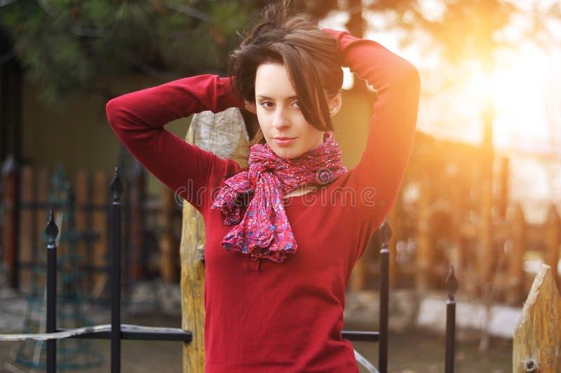 Schöne stilvolle junge Frau im roten Pullover des Schals, der allein gegen Yard aufwirft Berühren ihres Haares stockfoto