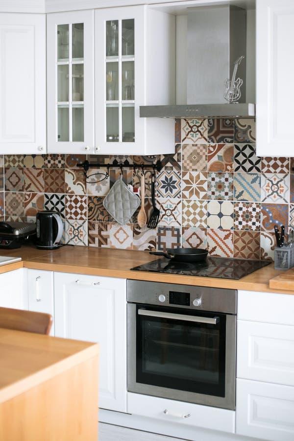 Schöne stilvolle weiße wirkliche Küche in der skandinavischen Art mit hölzerner Spitze und spanischen Fliesen lizenzfreie stockbilder