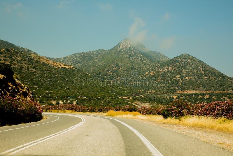 Schöne Straße in Kreta, mit vielen Blumen und Bergblick lizenzfreie stockfotos