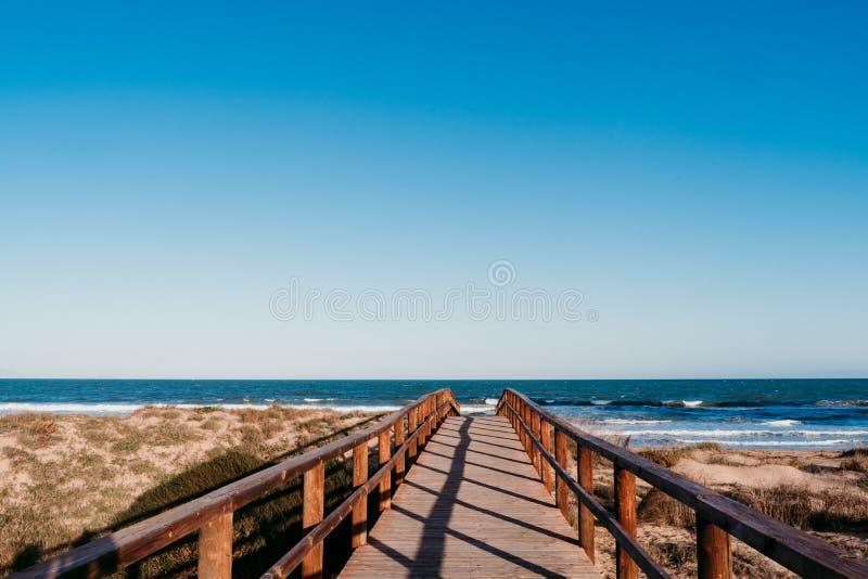 Schöne Strandlandschaft bei Sonnenuntergang Holzbrücke Blauer Himmel lizenzfreies stockbild