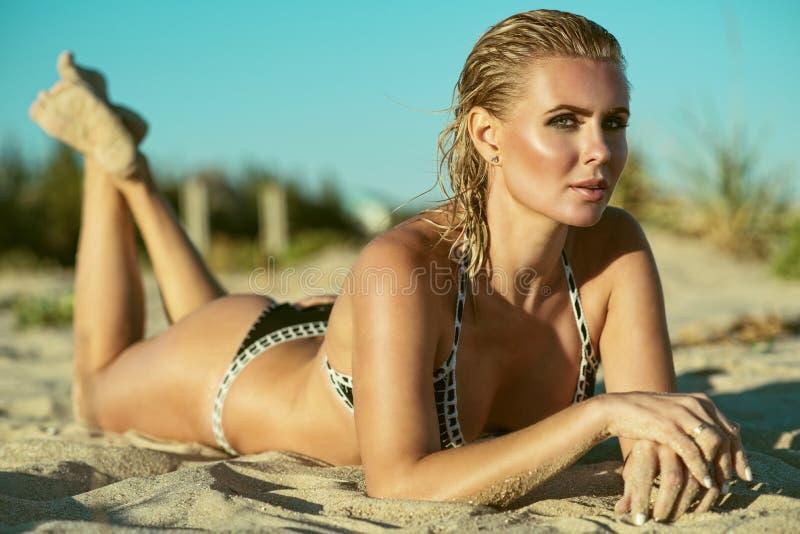 Schöne suntanned bezaubernde blonde Frau mit dem nassen Haar, das auf dem Strand und dem Genießen liegt stockfotografie