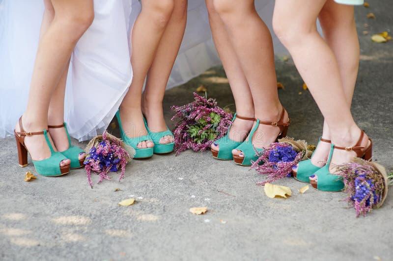 Schöne Türkisschuhe der Braut und der Brautjungfern und der Hochzeitsblumensträuße lizenzfreies stockbild