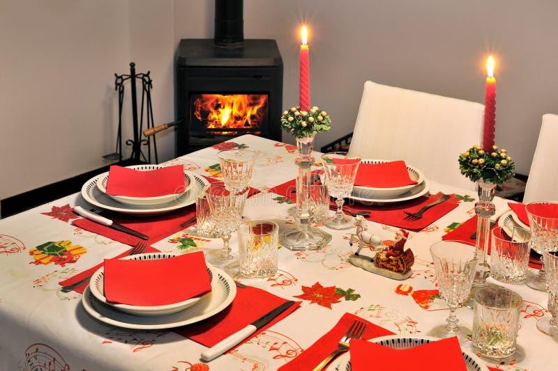 Schöne Tabelle des neuen Jahres mit hölzernem brennendem Ofen der roten Serviette auf Hintergrund stockfotografie