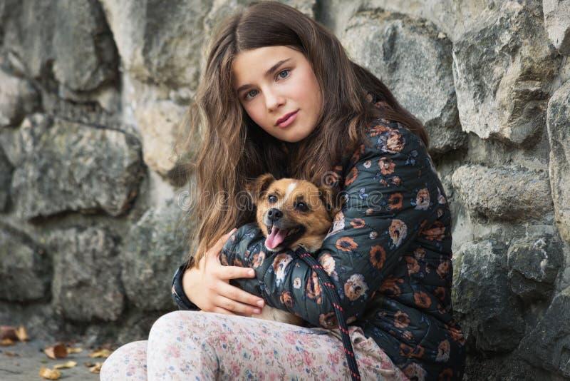 Schöne Teenager, die ihren neuen Haustier umarmt, Adoptivhund aus dem Notliegeplatz stockfotos