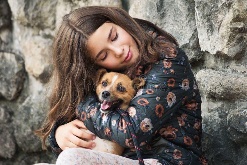 Schöne Teenager, die ihren neuen Haustier umarmt, Adoptivhund aus dem Notliegeplatz lizenzfreies stockfoto