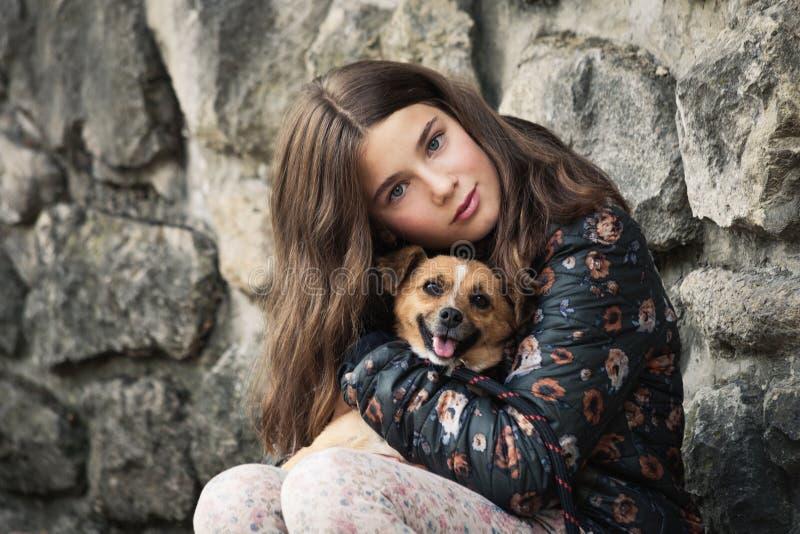 Schöne Teenager-Mädchen umarmt ihren neuen Freund-Hund aus dem Notliegeplatz lizenzfreies stockfoto
