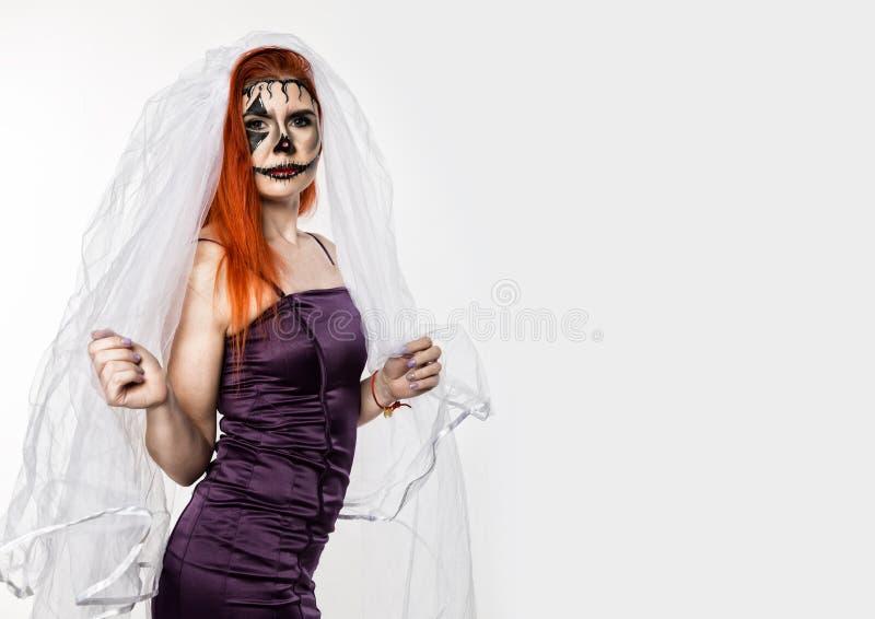 Schöne tote Braut mit der schrecklichen Maske gemalt auf ihrem Gesicht Halloween und kreatives Make-up stockfoto