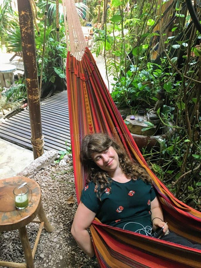 Schöne touristische Entspannung in einer Hängematte mit einem mojito in Flores stockfotos