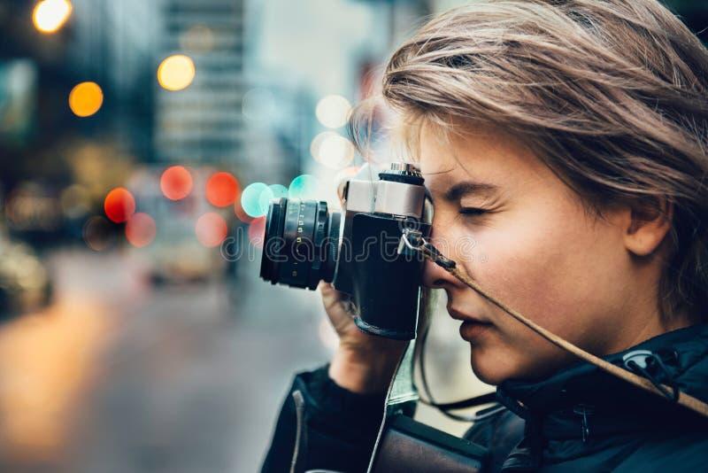 Schöne touristische Frau, die Foto mit alter Kamera der Weinlese in der Stadt macht stockbild