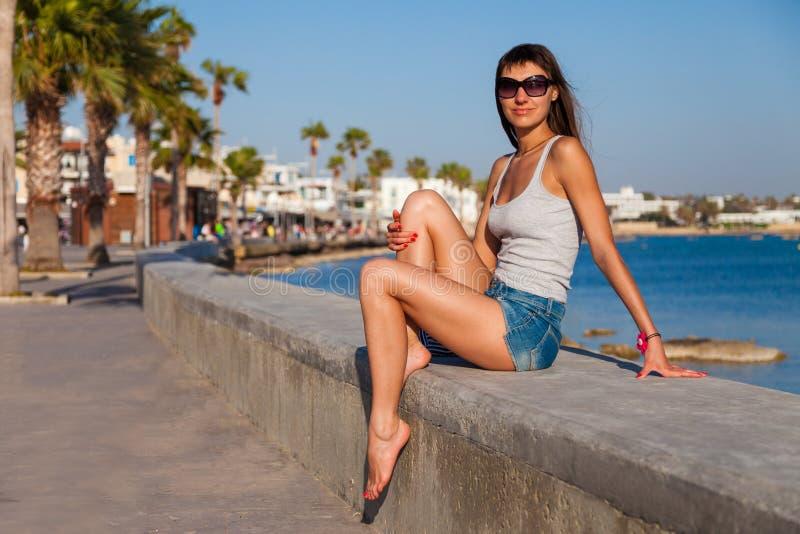Sch?ne touristische Frau nahe des alten Schlosses auf Mittelmeerk?ste Paphos, Zypern Helles Sonnenunterganglicht stockbilder