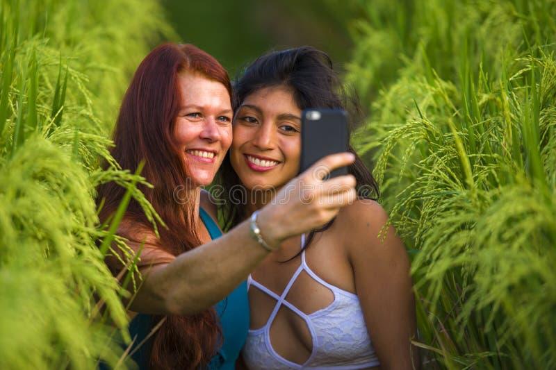 Sch?ne touristische Frauen, die Freundinnen selfie zusammen mit Handy in Reisfeldnatur-Landschaftsdem l?chelnden Genie?en nehmen stockbild