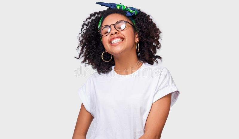Schöne träumerische dunkelhäutige junge Frau gekleidet im weißen T-Shirt, fühlend glücklich und genießen das Wetter stockbild