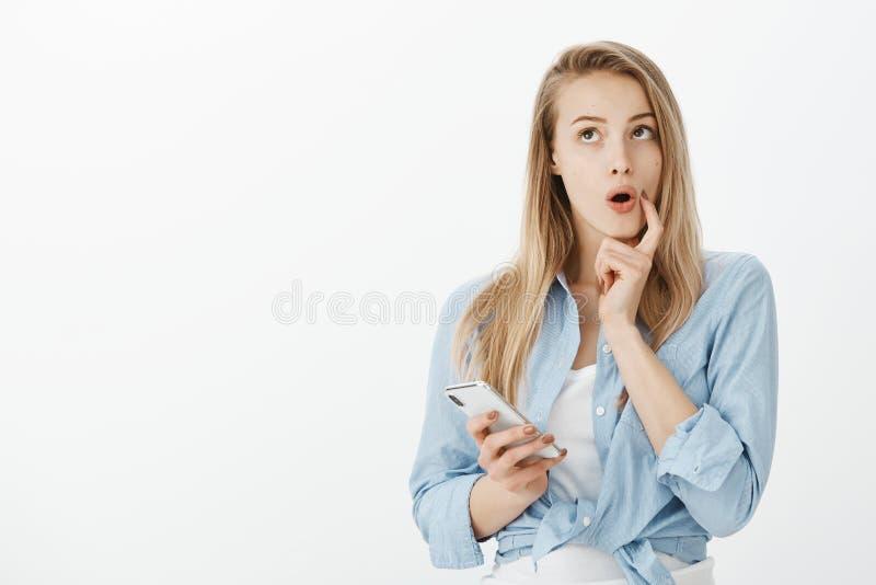 Schöne träumerische europäische Freundin in der stilvollen blauen Bluse, Smartphone halten, beißender Finger und aufwärts starren stockfotografie