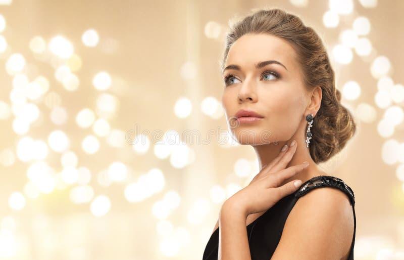 Schöne tragende Diamantohrringe der jungen Frau stockbilder