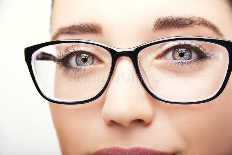 Schöne tragende Glasnahaufnahme der jungen Frau auf weißem Hintergrund stockfoto