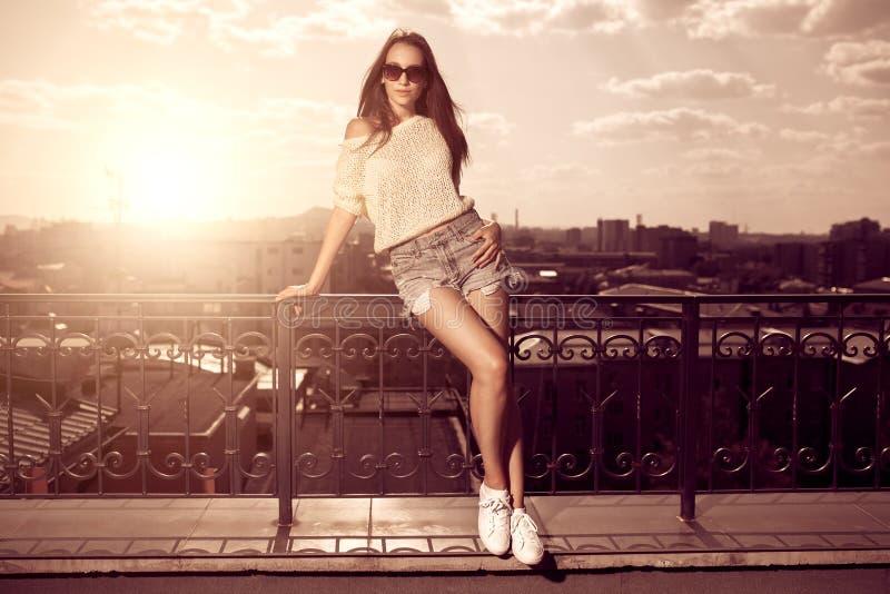 Schöne tragende Sonnenbrille der jungen Frau des Brunette, kurze Hosen, weiß stockfoto