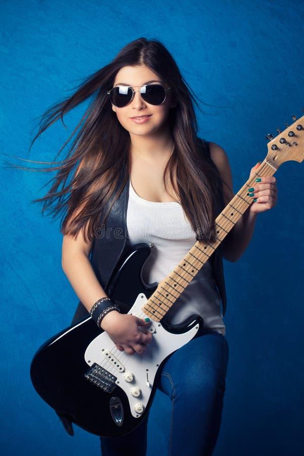 Schöne tragende Sonnenbrille der jungen Frau mit Gitarre lizenzfreie stockfotografie