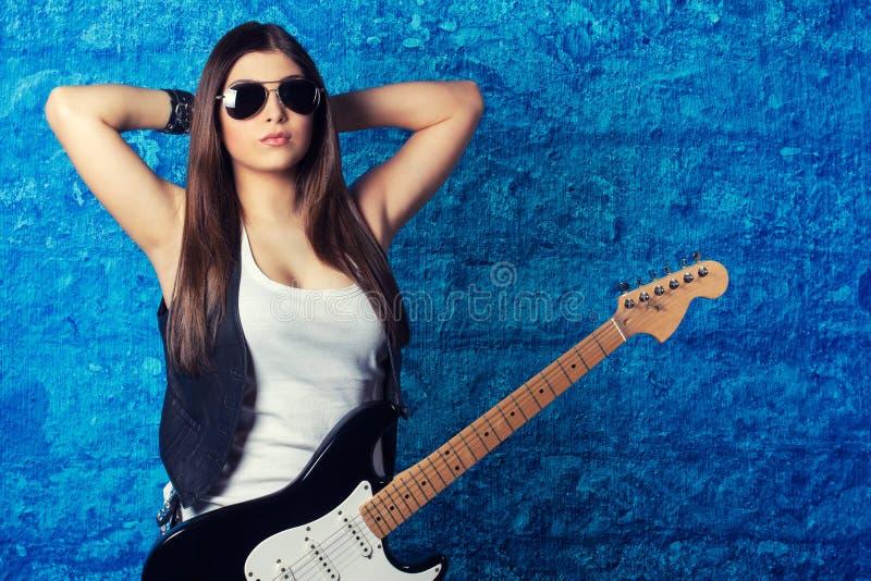Schöne tragende Sonnenbrille der jungen Frau mit Gitarre stockbild