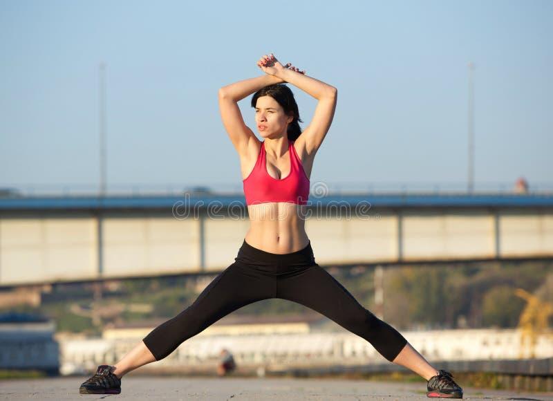 Schöne tragende Turnhallenkleidung der jungen Frau und ausdehnen Muskeln lizenzfreies stockbild