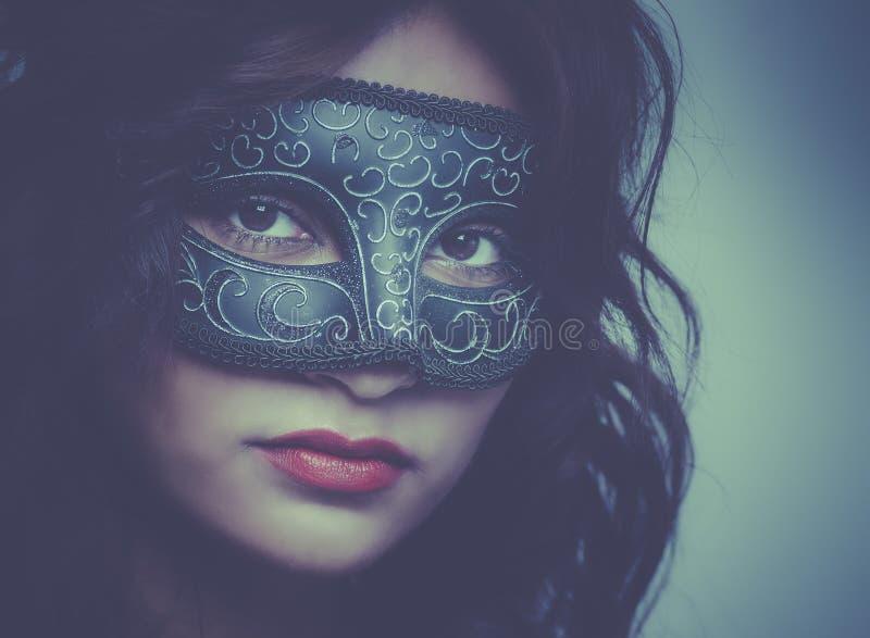 Schöne tragende venetianische Maske der jungen Frau lizenzfreies stockfoto