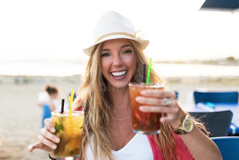 Schöne trinkende Erfrischung der jungen Frau auf dem Strand stockbild