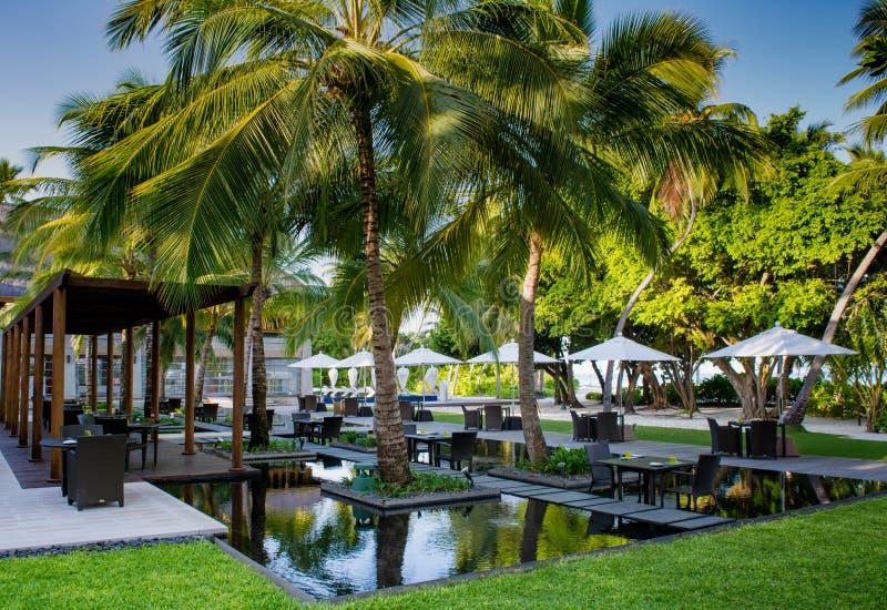 Schöne tropische Freienrestauranteinrichtung mit Tabellen im Wasser umgeben durch Palmen bei Malediven lizenzfreie stockbilder