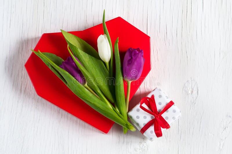 Schöne Tulpen auf einem roten Herzen Weißer hölzerner Hintergrund Mutter`s Tag Glücklicher Frauen ` s Tag stockbilder