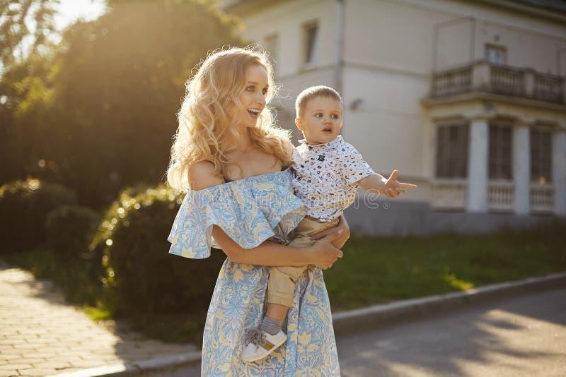 Schöne und überraschte junge Blondine im modernen blauen und gelben Kleid mit einem netten kleinen Baby auf ihren Händen lizenzfreie stockfotografie