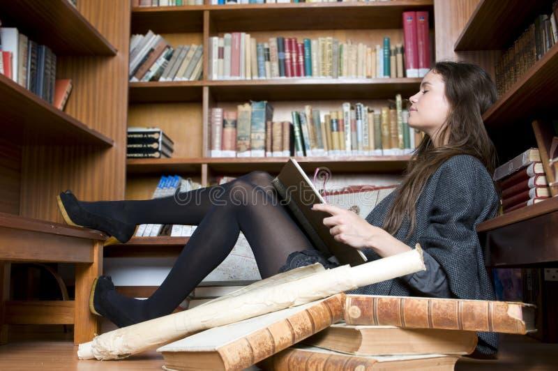 Schöne und Art und Weisefrau im Bibliotheksmesswert lizenzfreie stockfotos