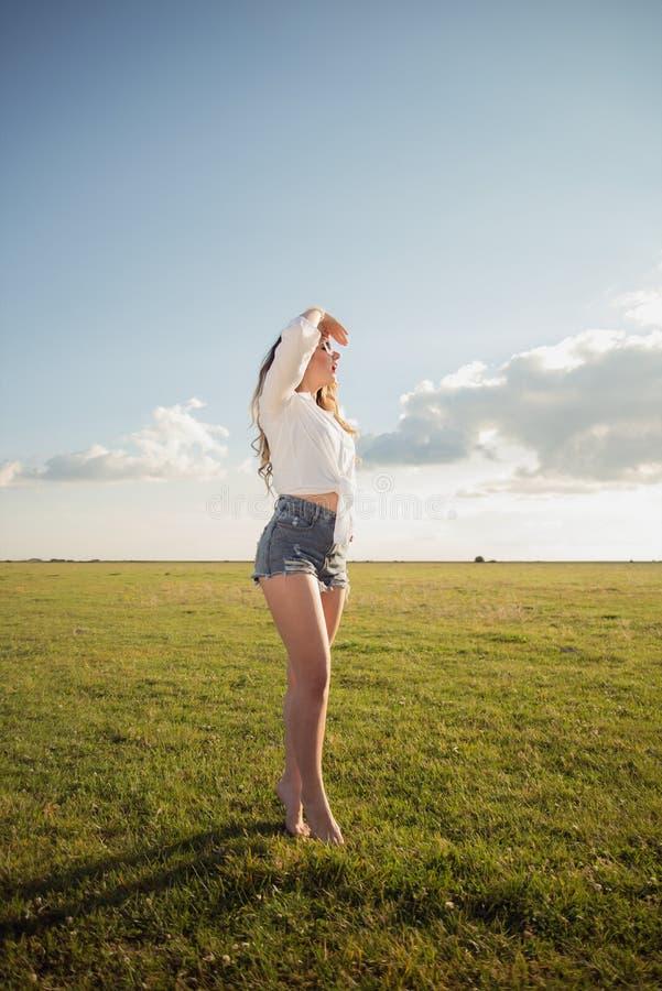 Schöne und attraktive Frau mit den sexy Beinen auf Grasschuh die Sonne mit ihrer Hand über ihren Augen weniger aufpassend lizenzfreie stockbilder