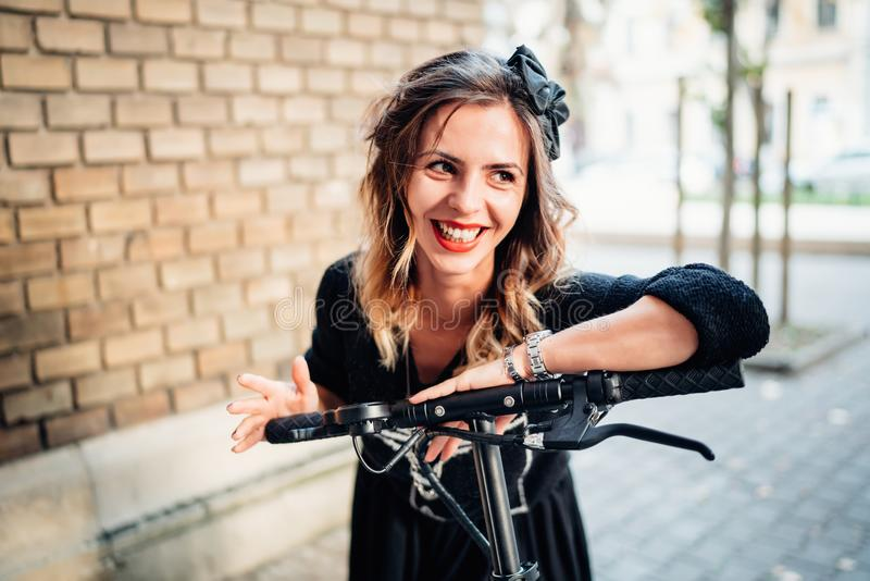 schöne und attraktive lächelnde Frau mit elektrischem Roller des modernen Stadttransportes stockfotos