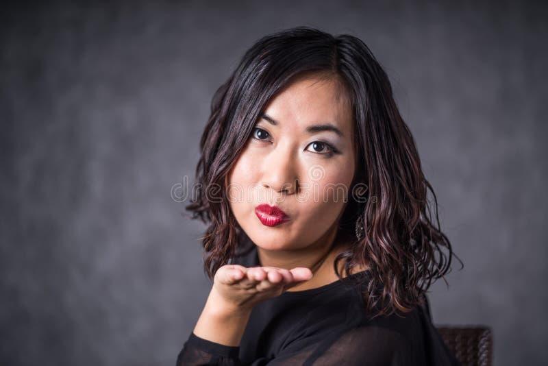 Schöne und attraktive reife junge asiatische einen Kuss durchbrennende und beim Tragen des Schwarzen lächelnde Brunette-Frau stockfotografie